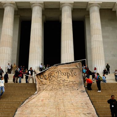 Volunteers unfurl a giant banner printed with the Preamble to the United States Constitution at the Lincoln Memorial.