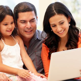 Hispanic family with laptop at home.