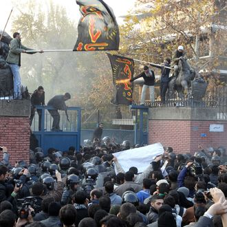 Iranian protesters gather outside the British embassy as some break into it and bring down the British flag (L) in Tehran on November 29, 2011. More than 20 Iranian protesters stormed the British embassy in Tehran, removing the mission's flag and ransacking offices.