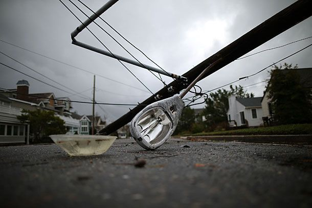 AVALON, NJ - OCTOBER 30: A street light and utility pole brought down from Hurricane Sandy lays on the street, on October 30, 2012 in Avalon, New Jersey. The storm has claimed at least 33 lives in the United States, and has caused massive flooding across much of the Atlantic seaboard. US President Barack Obama has declared the situation a 'major disaster' for large areas of the US East Coast including New York City, with wide spread power outages and significant flooding in parts of the city. (Photo by Mark Wilson/Getty Images)