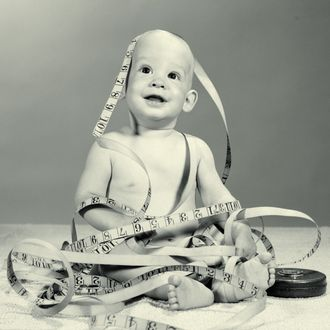 01 Jun 1964 --- 1960s smiling seated baby wrapped up in tangled tape measure --- Image by ? ClassicStock/Corbis