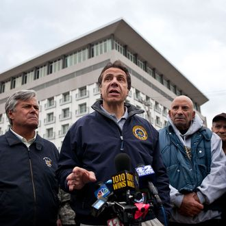 LONG BEACH, NY - OCTOBER 31: New York Governor Andrew Cuomo (3rd L) speaks to members of the media about recovering efforts after Hurricane Sandy, on October 31, 2012 in Long Beach, New York. Businesses across the eastern seaboard are attempting to return to normal operations as clean-up from Hurricane Sandy continues. (Photo by Andrew Burton/Getty Images)