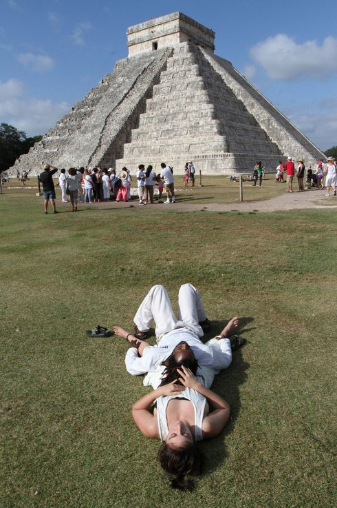 Two visitors are seen during a ritual ceremony around the Kukulkan Pyramid during the new cycle Mayan calendar celebration in the archaeological site of Chichen Itza, in Tinum municipality, in Yucatan State, southern Mexico, on Dec. 21, 2012.