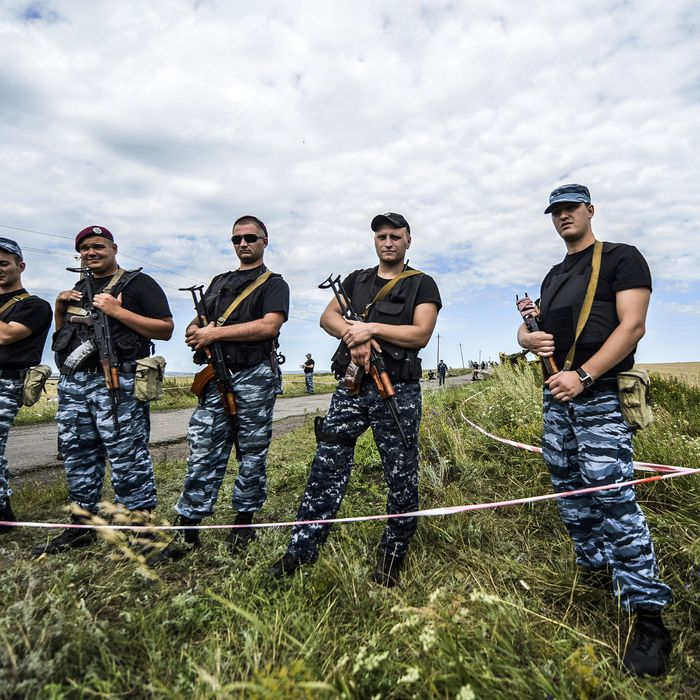 Armed pro-Russian separatists block the way to the crash site of Malaysia Airlines Flight MH17, near the village of Grabove, in the region of Donetsk on July 20, 2014. The missile system used to shoot down a Malaysian airliner was handed to pro-Russian separatists in Ukraine by Moscow, the top US diplomat said Sunday. Outraged world leaders have demanded Russia's immediate cooperation in a prompt and independent probe into the shooting down on July 17 of flight MH17 with 298 people on board. AFP PHOTO/ BULENT KILIC