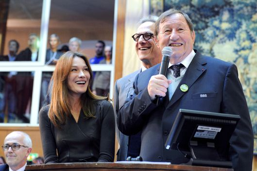 "Former French First Lady Carla Bruni-Sarkozy (L) and former coach of French L1 Auxerre's football club, Guy Roux (R) preside over the bidding for the prestigious ""piece du president"" (the chairman's item) during the 152th charity wine auction at the Hospices de Beaune on November 18, 2012 in Beaune, central France. The Hospices de Beaune charity wine auction is the oldest and most famous charity wine auction, whose funds collected are entirely destined for the institution's charities."