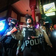 Police officers stand guard as people gather in front of the Ferguson Police Department on November 29, 2014 to protest against the Grand Jury's decision not to indict white Police Officer Darren Wilson in the shooting death of black 18-year old Michael Brown. (Photo by Cem Ozdel/Anadolu Agency/Getty Images)