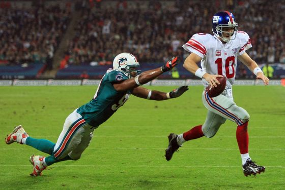 LONDON - OCTOBER 28:  New York quarterback, Eli Manning #10 outpaces Jason Taylor #99 of the Dolphins to score the opening touchdown during the NFL Bridgestone International Series match between New York Giants and  Miami Dolphins at Wembley Stadium on October 28, 2007 in London, England. This is the first ever regular season NFL match to be played outside of the United States.  (Photo by Richard Heathcote/Getty Images)