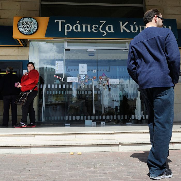 In this image taken Saturday, March 16, 2013, people queue to use an ATM machine outside of Bank of Cyprus branch in southern port city of Limassol, Saturday, March 16, 2013. Many rushed to cooperative banks which are open Saturdays in Cyprus after learning that the terms of a bailout deal that the cash-strapped country hammered out with international lenders includes a one-time levy on bank deposits. The move, decided in an extraordinary meeting of the finance ministers of the 17-nation eurozone in the early hours Saturday, is a major departure from established policies. Analysts have warned that making depositors take a hit threatens to undermine investors' confidence in other weaker eurozone economies and might possibly lead to bank runs.