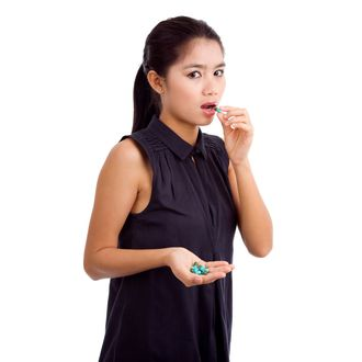 woman taking medicine, isolated on white background