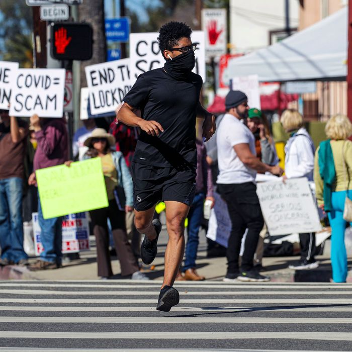 A man jogs by Covid vaccine and mask mandate protestors.