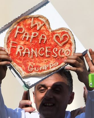 A man shows a pizza made for pope Francis during the weekly general audience in Saint Peter's square at the Vatican on March 11, 2015.