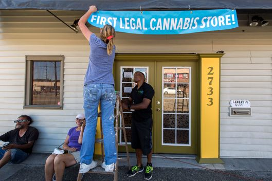July 7, 2014 - Seattle, Washington, U.S. -  ANDREW POWERS helps WENDY COOK put up a banner at Cannabis City, the sole dispensary in Seattle with a state license to sell recreational marijuana to the public on July 8, 2014, the first day of legal sales in the state of Washington.  Seated at left are the first two persons to secure a place in line, DEB GREENE and GEORGE VARGAS. (Credit Image: ? Brian Cahn/ZUMA Wire)