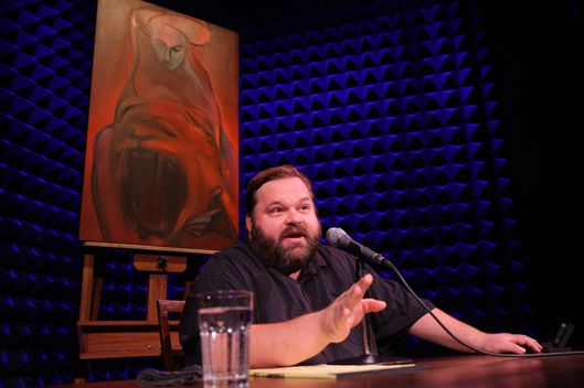 Mike Daisey in All the Faces of the Moon with the oil painting from Chapter 13, That Hideous Strength by artist Larissa Tokmakova, directed by Jean-Michele Gregory, running in Joe's Pub at The Public Theater through October 3.