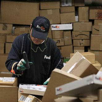 OAKLAND, CA - DECEMBER 13: A FedEx worker scans a pile of boxes at the FedEx sort facility at the Oakland International Airport on December 13, 2010 in Oakland, California. FedEx Corp. is predicting that Monday will be the busiest day in company history for delivering packages worldwide with an expected 16 million shipments, up close to 13% from last year's biggest shipping day. (Photo by Justin Sullivan/Getty Images)