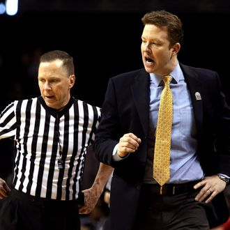 Head coach Chris Mooney of the Richmond Spiders speaks to a referee in the second half against the Charlotte 49ers during the first round of the Atlantic 10 basketball tournament at Barclays Center on March 14, 2013 in New York City.