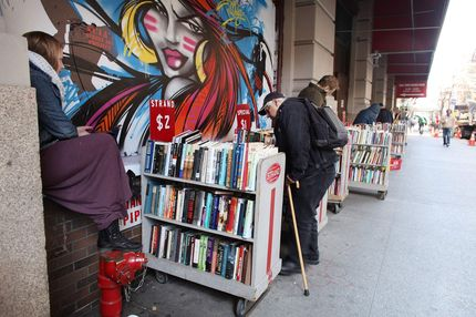 People browse through books outside of the Strand Bookstore on April 2, 2012 in New York City. Workers and owners of the Strand are in a contract dispute over healthcare contributions, a two-tier wage system and other benefits. Part of the United Autoworker's Union, the store's 140 non-management employees will vote on a new contract this week.