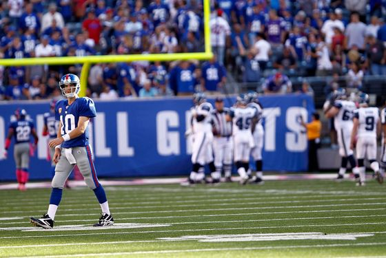 EAST RUTHERFORD, NJ - OCTOBER 09:   Eli Manning #10 of the New York Giants walks to the bench after throwing an interception that went for a touchdown during a game against the Seattle Seahawks at MetLife Stadium on October 9, 2011 in East Rutherford, New Jersey.  (Photo by Jeff Zelevansky/Getty Images)