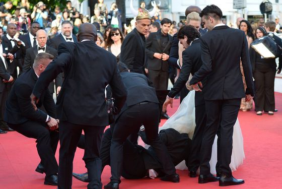 "Ukrainian journalist Vitalii Sediuk is blocked by minders as he tries to slip under US actress America Ferrera's dress as she arrives for the screening of the animated film ""How to train your Dragon 2"" at the 67th edition of the Cannes Film Festival in Cannes, southern France, on May 16, 2014."