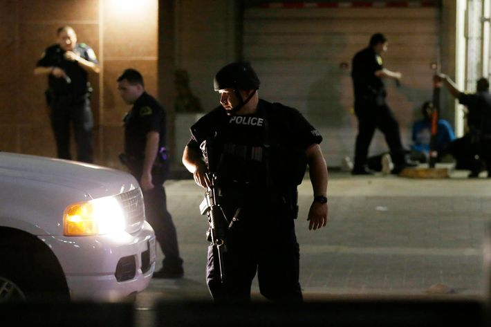 Dallas police detain a driver after several police officers were shot in downtown Dallas, Thursday, July 7, 2016. Snipers apparently shot police officers during protests and some of the officers are dead, the city's police chief said in a statement. (AP Photo/LM Otero)