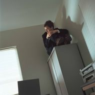 Businessman sitting on filing cabinet, looking out window