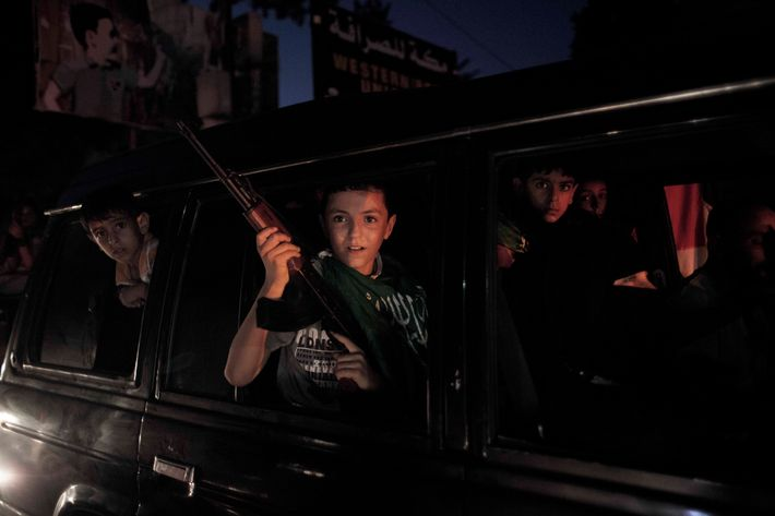 A boy holds with a banner and a rifle drives up a mainstreet in Gaza city as the ceasefire celebrations begins.