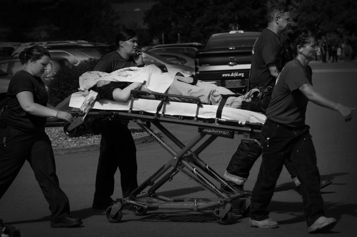 Authorities carry a shooting victim away from the scene after a gunman opened fire at Umpqua Community College in Roseburg, Ore., Thursday, Oct. 1, 2015. (Mike Sullivan/Roseburg News-Review via AP)