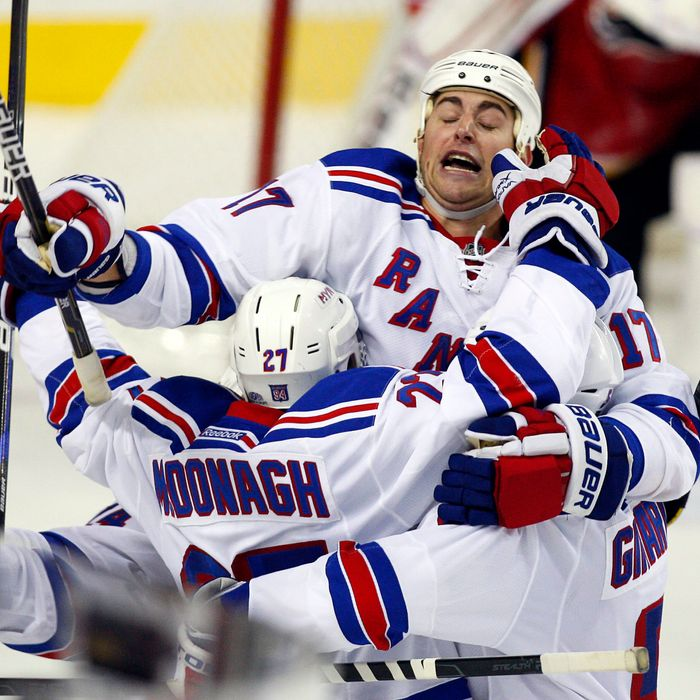 New York Rangers' Ryan McDonagh, bottom left, celebrates his overtime goal with Brandon Dubinsky, top, and another player, in an NHL hockey game against the Calgary Flames in Calgary, Alberta, Thursday, Oct. 20, 2011. The Rangers won 3-2. (AP Photo/The Canadian Press, Jeff McIntosh)