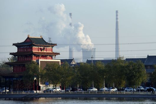 "A building newly built in the architecture of imperial China stands near the cooling towers and smokestack chimneys of a coal-fired power plant on the outskirts of Beijing on November 15, 2010. The spread of consumerism among China's burgeoning middle class is behind the rapid growth of the Asian giant's environmental footprint, the World Wildlife Fund said in its annual ""China Ecological Footprint"" report, as demand for construction, transport, goods and public services being key factors behind ballooning carbon emissions. Carbon emissions accounted for 54 percent of China's ecological footprint in 2007 and the country needed more than two times its own biologically productive land area to meet demand for resources and to absorb emissions, the WWF said, while defining ""ecological footprint"" as the amount of stress a country places on world ecosystems. AFP PHOTO/Frederic J. BROWN (Photo credit should read FREDERIC J. BROWN/AFP/Getty Images)"