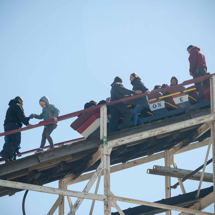 Workers assist thrill seekers on the Luna Park Coney Island Cyclone roller coaster after it got stuck on its inaugural run of the Summer 2015 season. The rescue involved walking down the ties. -- The Coney Island Cyclone roller coaster got stuck on its inaugural run of the Summer season. The train stopped just short of the initial drop. The first riders had to escorted down the landmark wooden coaster after being stuck for about 5 minutes.