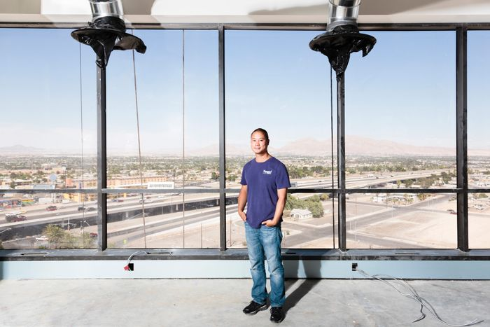 Tony Hsieh stands in front of large windows that look out onto a construction site in Las Vegas.