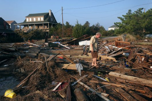 NAGS HEAD, NC - AUGUST 28:  Billy Stinson searches for his belonging in a pile of debris that was once his cottage August 28, 2011 in Nags Head, North Carolina. The cottage, built in 1903 and destroyed yesterday by Hurricane Irene, was one of the first vacation cottages built on Albemarle Sound in Nags Head. Stinson has owned the home, which is listed in the National Register of Historic Places, since 1963.  (Photo by Scott Olson/Getty Images)