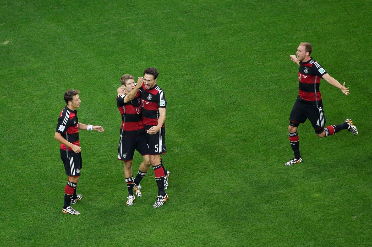 BELO HORIZONTE, BRAZIL - JULY 08:  Thomas Mueller of Germany celebrates scoring his team's first goal with Mats Hummels, Mesut Oezil (L) and Benedikt Hoewedes (R) during the 2014 FIFA World Cup Brazil Semi Final match between Brazil and Germany at Estadio Mineirao on July 8, 2014 in Belo Horizonte, Brazil.  (Photo by Felipe Dana - Pool/Getty Images)