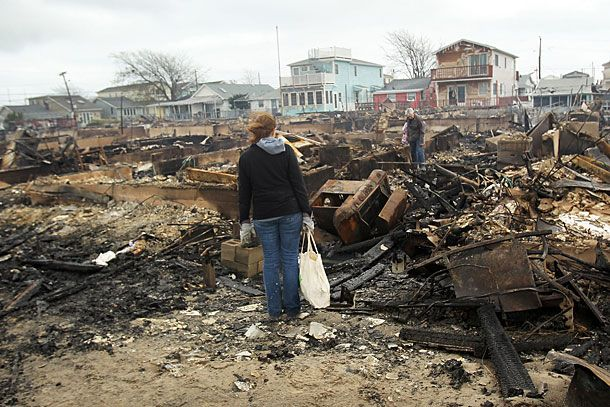 NEW YORK, NY - OCTOBER 30:  People look through the remains of homes destroyed during Hurricane Sandy October 30, 2012 in the Breezy Point neighborhood of the Queens borough of New York City. At least a few dozen people were reported killed in the United States by Sandy as millions of people in the eastern United States have awoken to widespread power outages, flooded homes and downed trees. New York City was hit especially hard with widespread power outages and significant flooding in parts of the city.  (Photo by Spencer Platt/Getty Images)