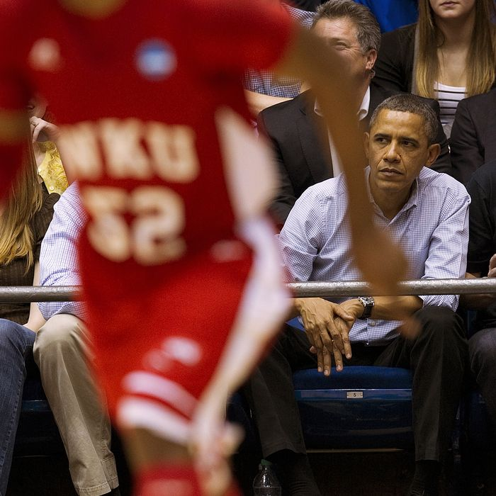 US President Barack Obama (2nd R) and British Prime Minister David Cameron (R) watch Mississippi Valley State University play against Western Kentucky University at the University of Dayton Arena in Dayton, Ohio, March 13, 2012.