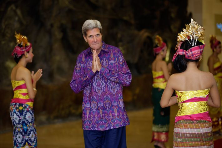 """US Secretary of State John Kerry, wearing an """"endek,"""" a traditional Balinese woven fabric, poses upon arrival for a gala dinner hosted for the leaders at the Asia-Pacific Economic Cooperation (APEC) Summit in Nusa Dua on the Indonesian resort island of Bali on October 7, 2013."""