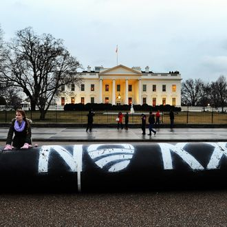 Environmental activists inflate a long balloon to mock a pipeline during a demonstration in front of the White House in Washington, DC, on February 3, 2014 to protest against the Keystone pipeline project.