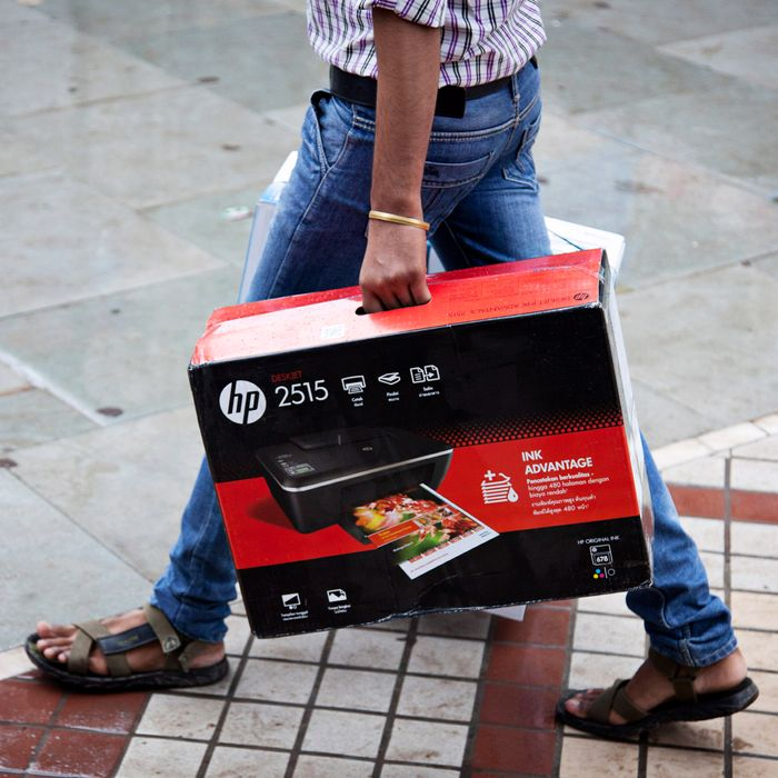 A man carries a boxed Hewlett-Packard Co. 2515 printer in Nehru Place IT Market, a hub for the sale of electronic goods and computer accessories, in downtown New Delhi, India on Wednesday Aug. 7, 2013. India's consumer price index (CPI) figures for July are scheduled to be released on August 12.