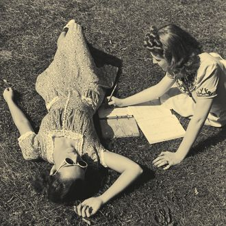 Two teenage girls (14-16) on grass, one doing homework (B&W)