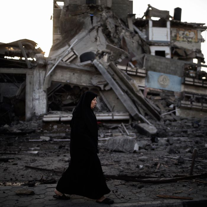 A Palestinian woman walks past a house destroyed during an Israeli airstrike, on November 20, 2012. Israeli leaders discussed an Egyptian plan for a truce with Gaza's ruling Hamas, reports said, before a mission by the UN chief to Jerusalem and as the toll from Israeli raids on Gaza rose over 100.