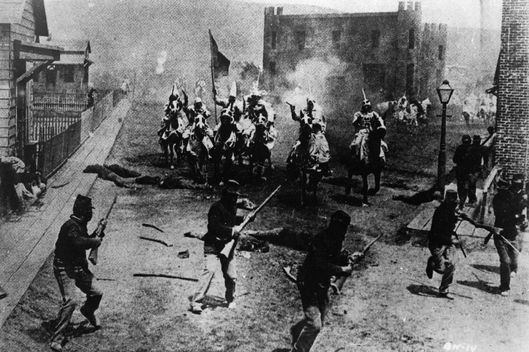 Ku Klux Klan members on horseback drive a black militia out of town in a battle scene from 'The Birth of a Nation,' the first-ever feature-length film, directed by D. W. Griffith, 1914.