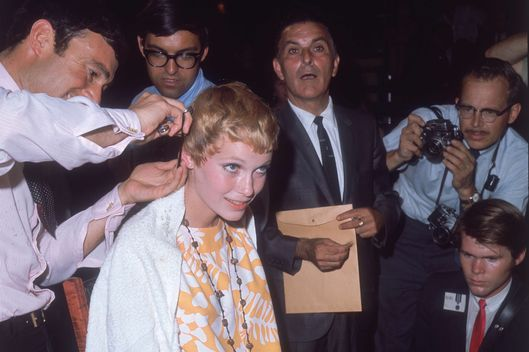 1967:  American actor Mia Farrow gets a haircut by stylist Vidal Sassoon while surrounded by photographers.