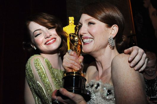 Nominee for Best Supporting Actress Emma Stone (L) embraces Winner for Best Actress Julianne Moore at the Governor's Ball following the 87th Oscars February 22, 2015 in Hollywood, California. AFP PHOTO / VALERIE MACON        (Photo credit should read VALERIE MACON/AFP/Getty Images)