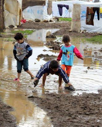 Syrian refugee kids play in the mud after rain as rain and winter worsens the living conditions of Syrian refugees living in a refugee camp in Akkar, Lebanon on January 02i 2014.