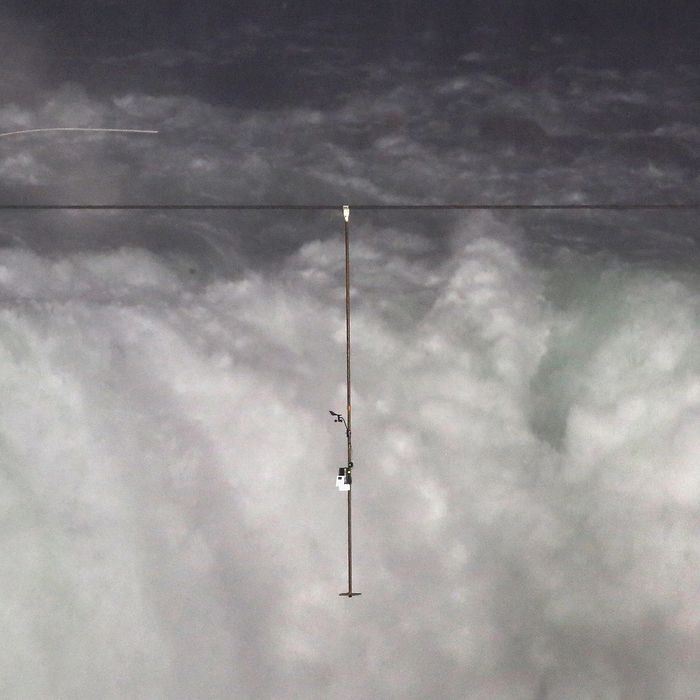 NIAGARA FALLS, NY - JUNE 15: Aerialist Nik Wallenda tighropes over the Niagara Falls June 15, 2012 in Niagara Falls, New York. Wallenda walked across the 1,800 foot 2 inch-wide wire Friday night as the first person to cross directly over the falls from the U.S. into Canada. Wallenda, 33 and a father of three, is a seventh generation member of the famed Flying Wallendas who trace their roots to 1780 Austria-Hungary, when ancestors traveled as a band of acrobats, aerialists, jugglers, animal trainers and trapeze artists. ABC televised the event and insisted the daredevil wear a teathered harness to prevent live coverage of a potentially deadly fall 190 feet into the churning torrent below. (Photo by John Moore/Getty Images)
