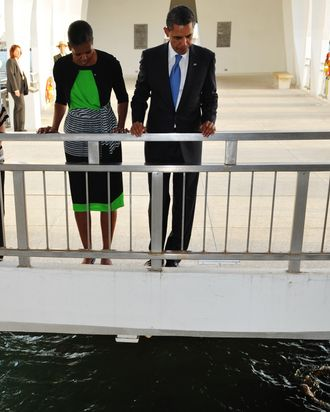 US President Barack Obama and First Lady Michelle Obama pay their respects at the USS Arizona Memorial at Pearl Harbor December 29, 2011 in Honolulu, Hawaii. AFP PHOTO/Mandel NGAN (Photo credit should read MANDEL NGAN/AFP/Getty Images)