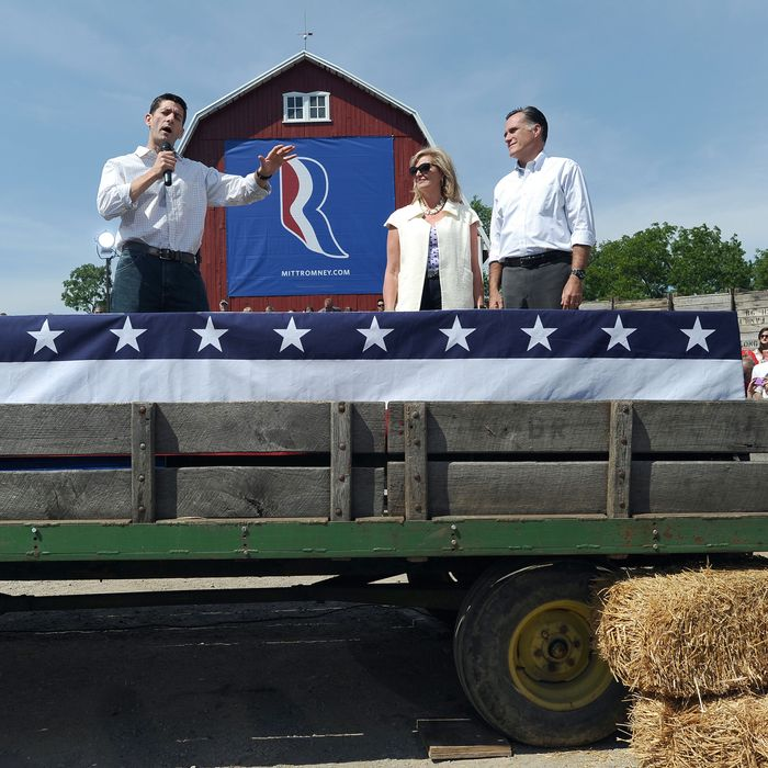 US Republican presidential candidate Mitt Romney and wife Ann look on as his running mate Paul Ryan speaks during a campaign event at a farm in Commerce, Michigan, on August 24, 2012.
