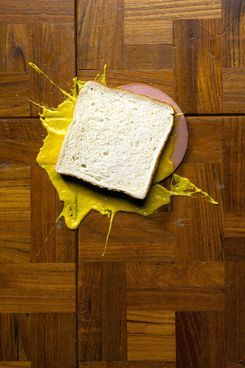 A baloney sandwich with mustard dropped on the floor