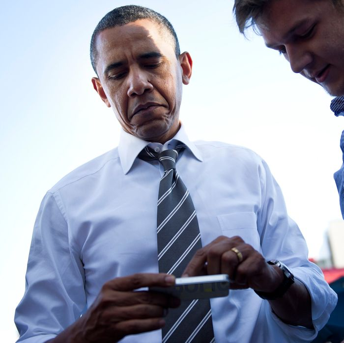 US President Barack Obama looks at a persons iPhone outside The Sink Restaurant and Bar April 24, 2012 in Boulder, Colorado.