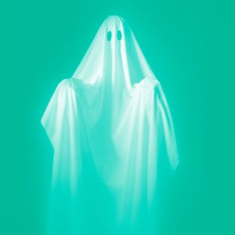 CIRCA 1960s: Person Wearing A Ghost Costume, Made Out Of A White Sheet With Two Holes In It. Highlights Are On The Sheet, The Background Is Pitch Black.