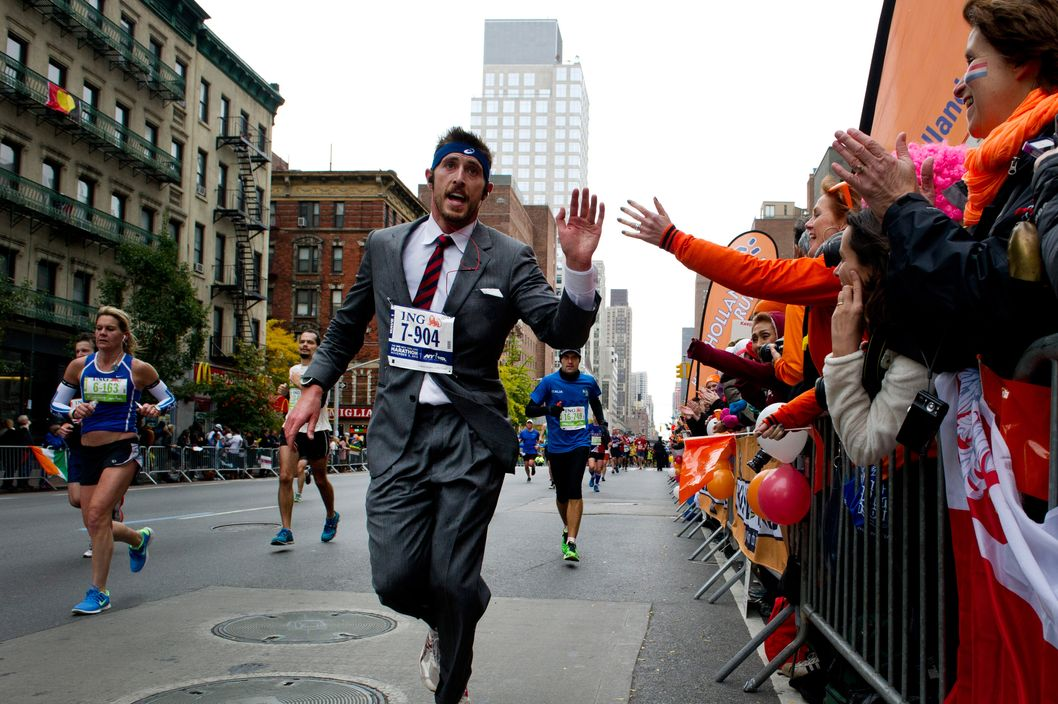 A man in a suit runs up First Avenue November 3, 2013 during the running of the New York City Marathon in New York.